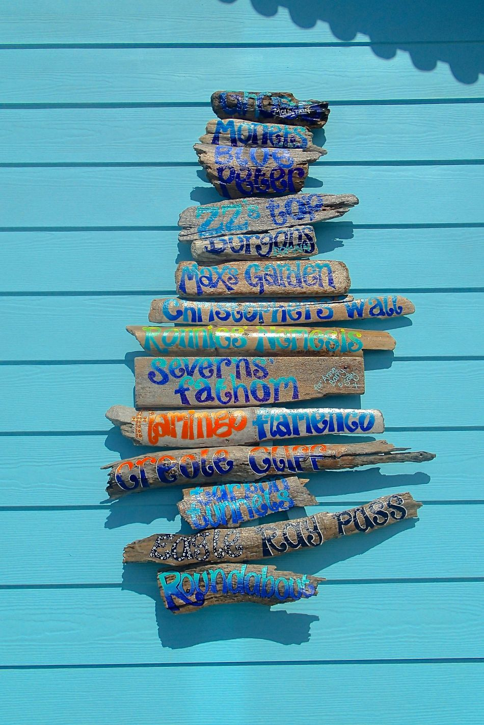 Kate's hand painted driftwood, detailing North Wall dive sites.